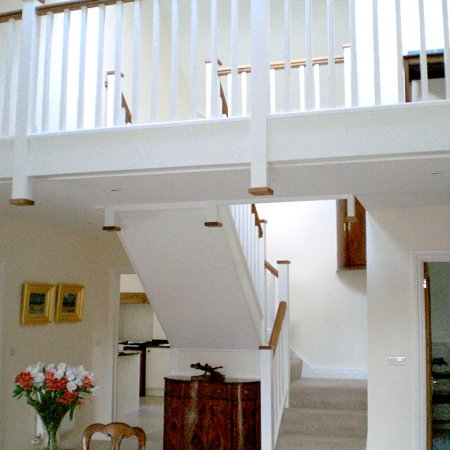 Painted staircase with hardwood handrail and matching balcony