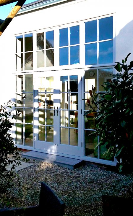 Pair of glazed doors with matching side light and windows above.
