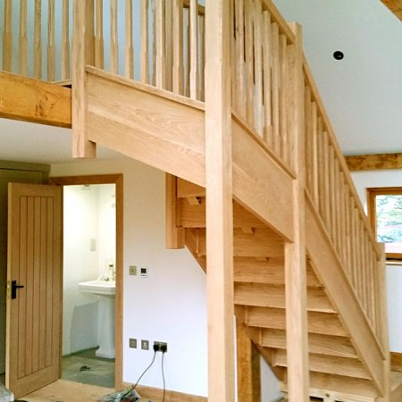 Oak staircase in a barn going up to an open balcony